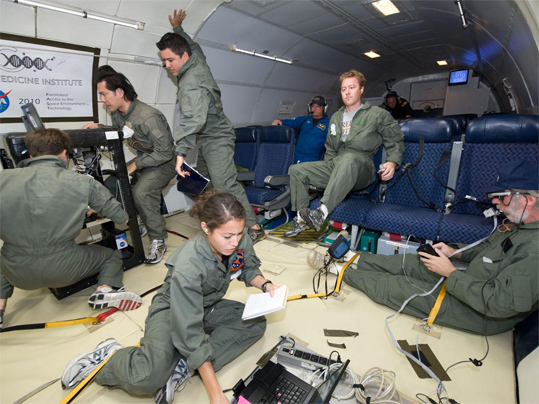 Experiments were performed in the flight cabin among 16 other groups also selected for the flights. Three DMI/GRC team members are shown at left under the DMI banner.